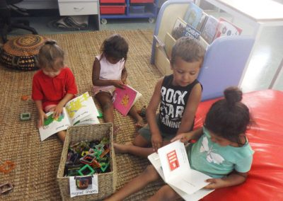 Four toddlers reading on the floor in the classroom