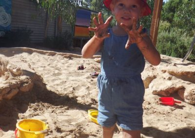 Toddler playing in sand pit with hands up