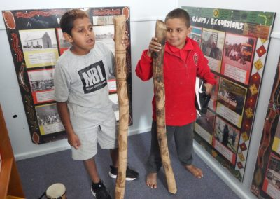 Two students holding a didgeridoo